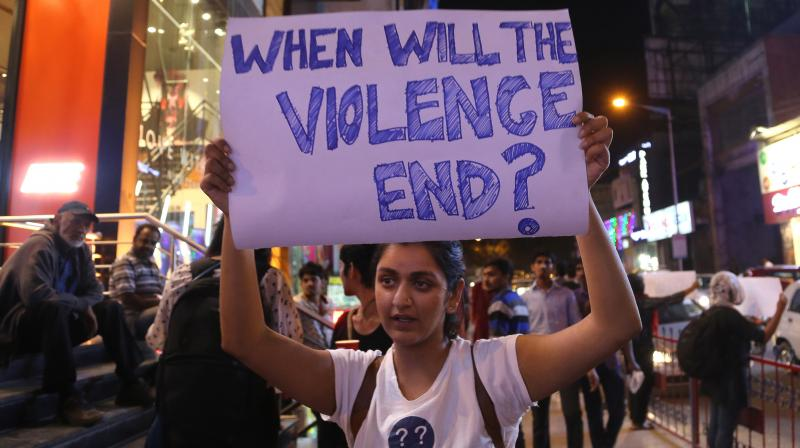 An Indian student holds a placard during a protest against the alleged molestation of a Tanzanian girl, in Bangalore, India. (Photo: AP)
