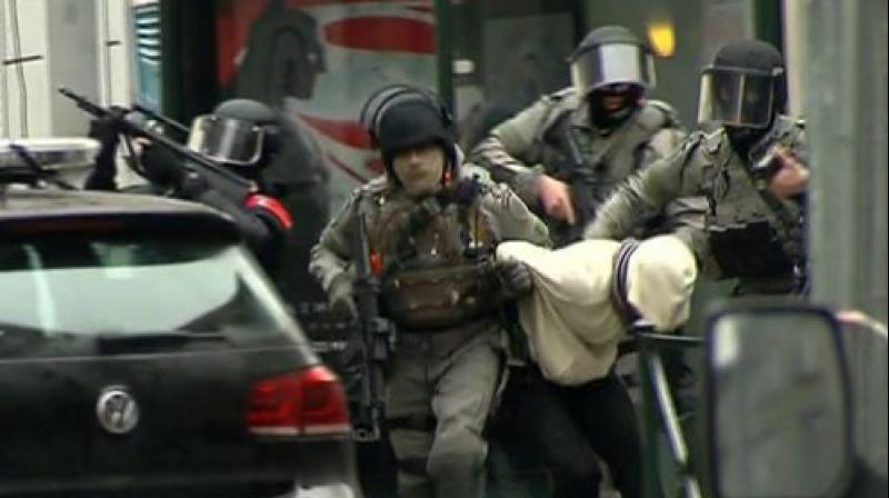 Armed police officers escort a suspect to a police vehicle during a raid in the Molenbeek neighborhood of Brussels, Belgium in connection with the Paris attacks. (Photo: AP)