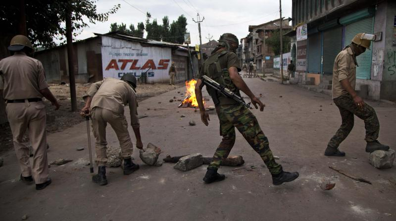Indian policemen remove rocks placed by Kashmiri protesters to block a road during a protest in Srinagar. (Photo: AP)