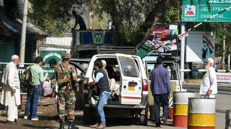An Army person inspects a passenger vehicle at the checkpost near Uri Army Brigade. (Photo: PTI)