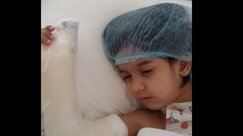 Three-year-old Myra lies in a hospital bed after her thumb was amputated. (Photo: Facebook)