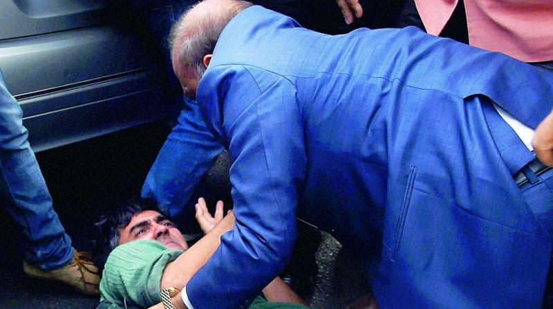 BJP MLA O.P. Sharma thrashes one of the JNU students who were protesting against the arrest of JNUSU president Kanhaiya Kumar outside the Patiala House Courts in New Delhi on Monday. (Photo: PTI)