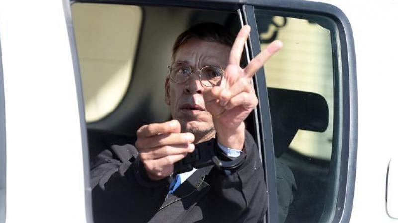 Seif al-Din Mohamed Mostafa, an Egyptian man who hijacked an EgyptAir passenger plane the previous day and forced it to divert to Cyprus demanding to see his ex-wife, flashes the 'V' for victory sign as he leaves the court in Larnaca. (AFP Photo)