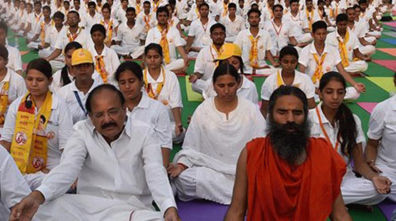 Yoga exponent Ramdev and Union Minister Venkaiah Naidu practice Yoga along with others during a yoga camp ahead of the International Yoga Day on June 21, at Rajpath in New Delhi.