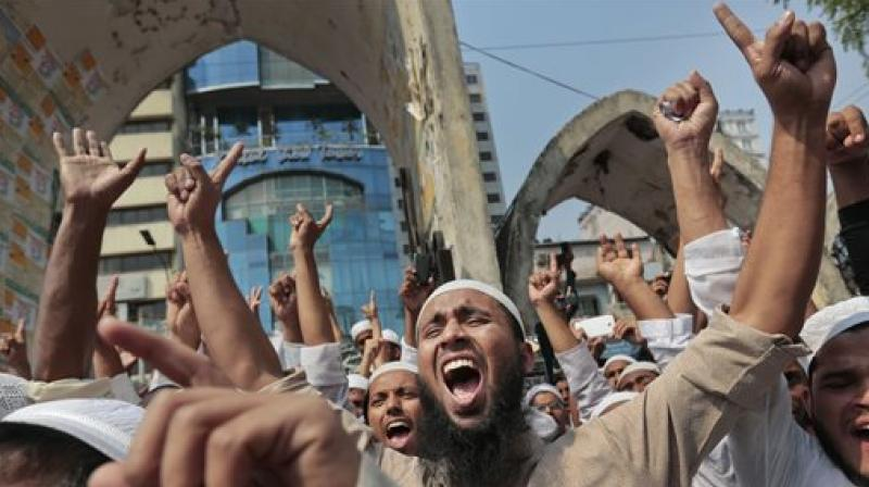 Bangladeshi activists of various Islamic political groups and other Muslims shout slogans after Friday prayers during a protest in Dhaka, Bangladesh. Thousands of Muslim devotees have rallied in Bangladesh's capital to denounce a court petition seeking to remove Islam as state religion in the Muslim-majority South Asian nation which is ruled by secular laws. (Photo: AP)