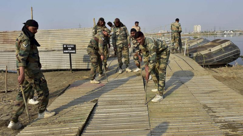 Army personnel construct temporary bridges over Yamuna river for the three-day World Peace Festival organised by spiritual guru Sri Sri Ravi Shankar in New Delhi. (Photo: PTI)