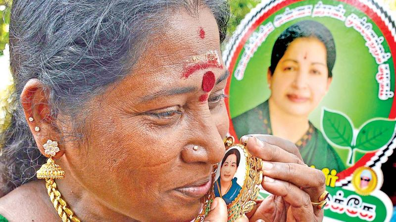 An AIADMK cadre fondly kisses a dollar chain with Jayalalithaa's photo to celebrate the party's win on Thursday. 	—DC