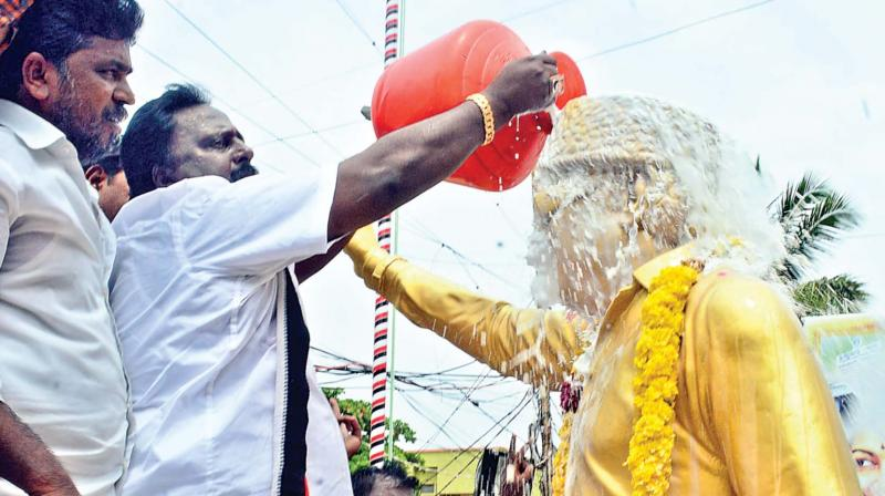 Cadres pour milk on the founder MGR's statue at party  headquarters.