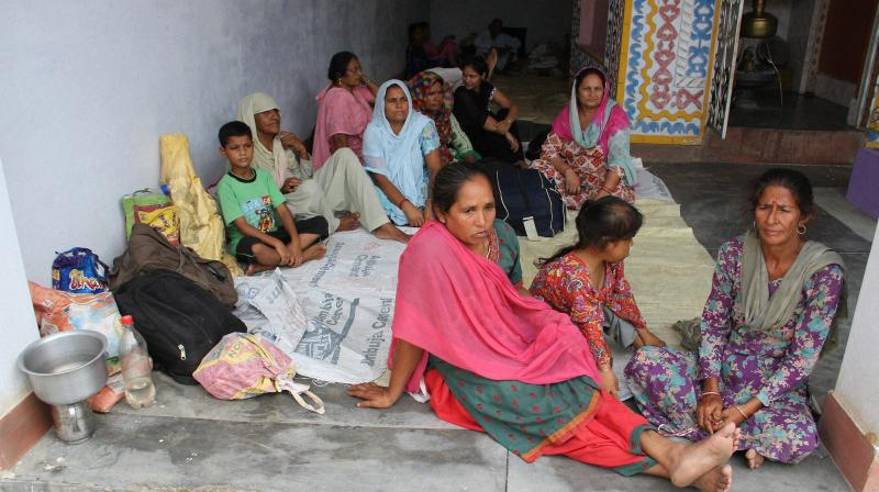 Villagers of Pallawala border take shelter at a temple of Akhnoor sector, Jammu and Kashmir. (Photo: PTI)