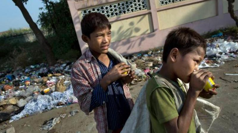 Street children sniff glue in the foreground of a roadside garbage dump in Hlaing Tharyar, northwest of Yangon, Myanmar. (Photo: AP)