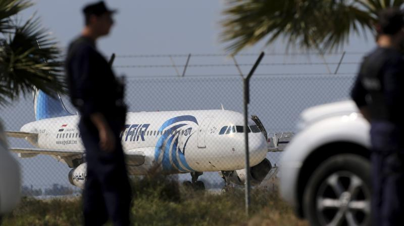 Police officers stand guards by the fence of the airport as a hijacked EgyptAir aircraft is seen after landing at Larnaca Airport in Cyprus. (Photo: AP)