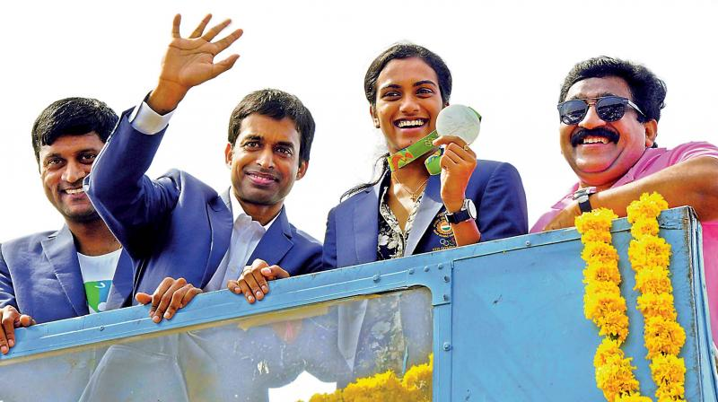 Pullela Gopichand waves to the crowd while P.V. Sindhu displays her Olympic silver medal during an open-top bus parade in Hyderabad on Monday, after her arrival in the city.