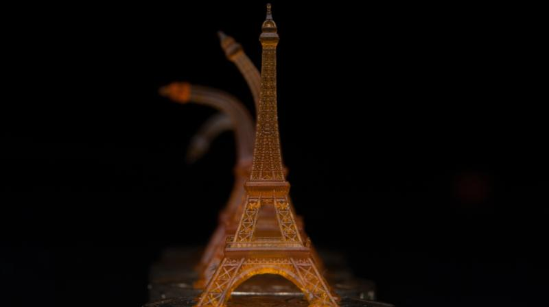 A shape-memory Eiffel tower was 3-D printed using projection microstereolithography. It is shown recovering from being bent, after toughening on a heated Singapore dollar coin.