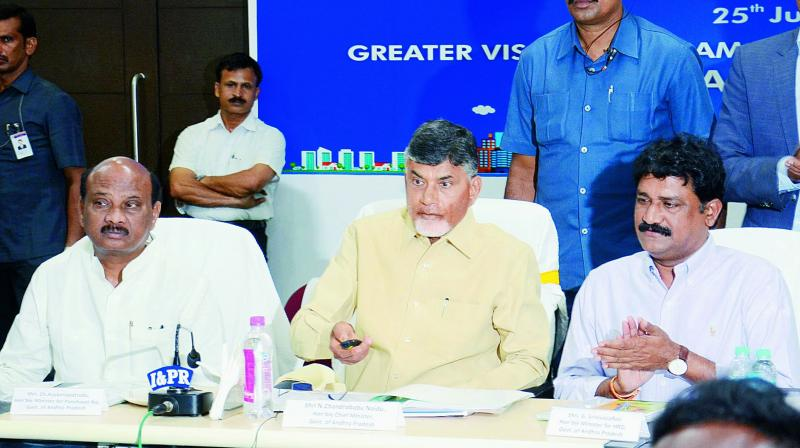 Chief Minister N. Chandra Babu Naidu inaugurates Command Control Centre Video Wall with the help of a remote during a meeting on the launch of projects on Smart City Missions at GVMC in Visakhapatnam on Saturday. Ministers Ganta Srinivasa Rao and Ch Ayyanna Patrudu are also seen.