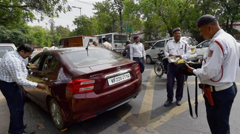 Traffic police men slap a challan to a commuter for riding with number plate ending with an even digit in New Delhi on Friday. (Photo: PTI)