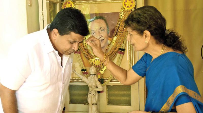 PTR's wife Rukmani blesses her son P. Thiagarajan before he leaves for campaign in Madurai Central Assembly constituency, in front of his father's photo at their residence in Madurai. (Photo: DC)