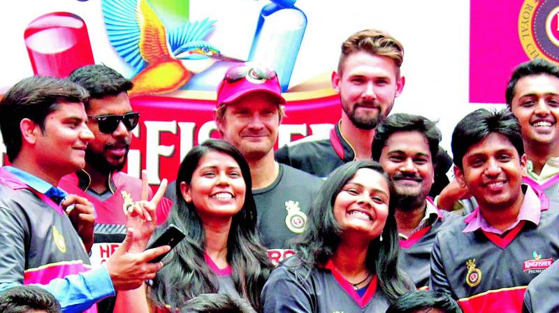 RCB players Varun Aaron (from left), Shane Watson and Kane Richardson pose with fans at a promotional event. (Photo: DC)