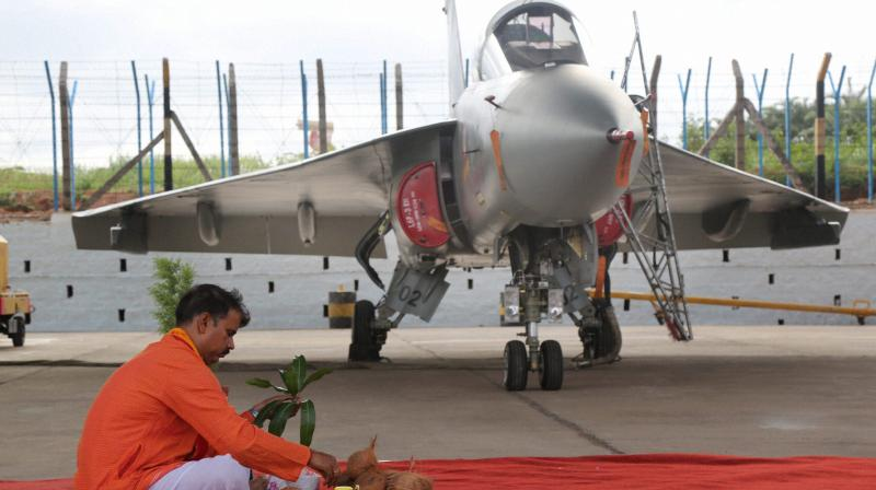A priest performs worship near Light Combat Aircraft (LCA) Tejas during a ceremony for its induction into the IAF, at HAL (ASTE) in Bengaluru. (Photo: PTI)