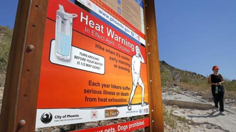 A sign warning of extreme heat is seen on a trailhead at Piestewa Peak in Phoenix. (Photo:AP)