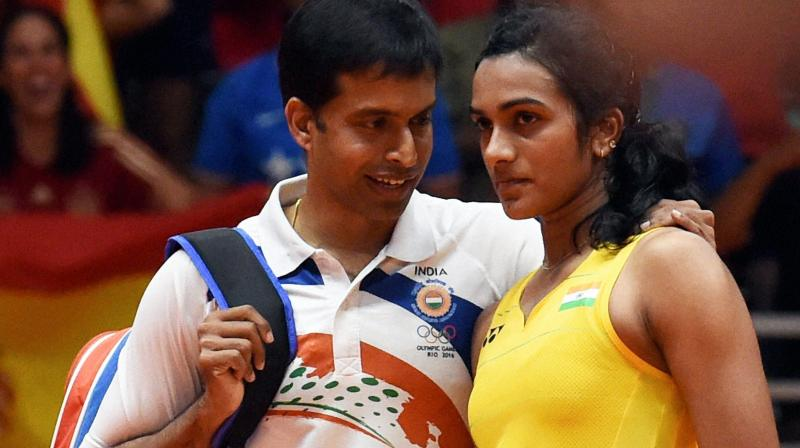 Pusarla V Sindhu with coach Pullela Gopichand after she lost against Spain's Carolina Marin in women's Singles final at the 2016 Summer Olympics at Rio de Janeiro in Brazil. (Photo: PTI)
