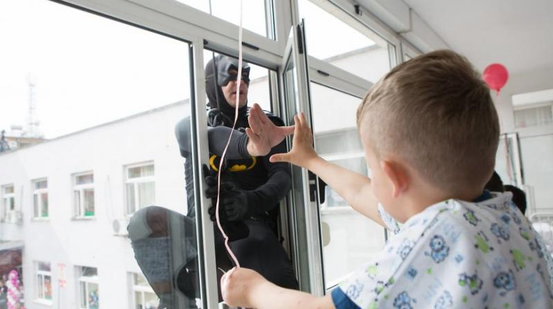 A police officer dressed as Batman shaking hands with a child patient at a hospital. (Photo: Facebook)
