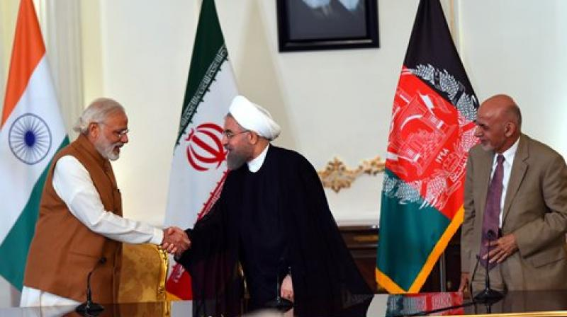 Prime Minister Narendra Modi shakes hands with Iranian President Hassan Rouhani as Ashraf Ghani, President of Afghanistan looks on after signing an agreement (Photo: PTI)