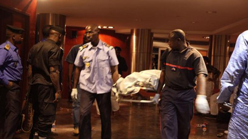 Mali security personal carry the body of a victim inside the Radisson Blu hotel after an attack. (Photo: AP)