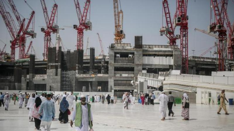 File photo of pilgrims walking outside the Grand Mosque in Mecca, Saudi Arabia. The giant construction firm, Saudi Binladin Group, has reportedly laid off 77,000 foreign workers. (Photo: AP)