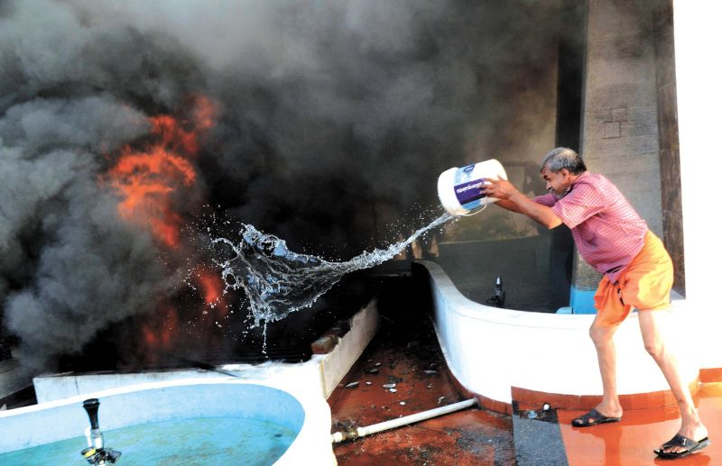 A senior citizen tries to douse the fire that broke out at a shopping complex in East Fort in Thiruvananthapuram on Sunday (Photo: PEETHAMBARAN PAYYERI)