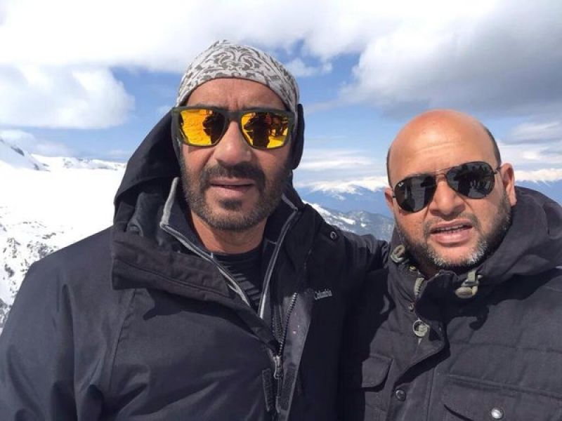 Ajay Devgn strikes a pose with a crew member of 'Shivaay'.