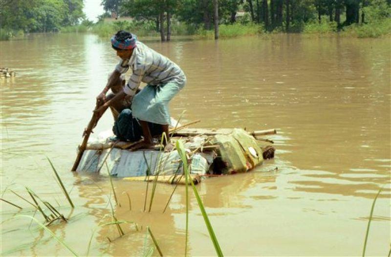 Flood victims use a raft to shift at Raghopur in Vaishali district of Bihar. (Photo: PTI)