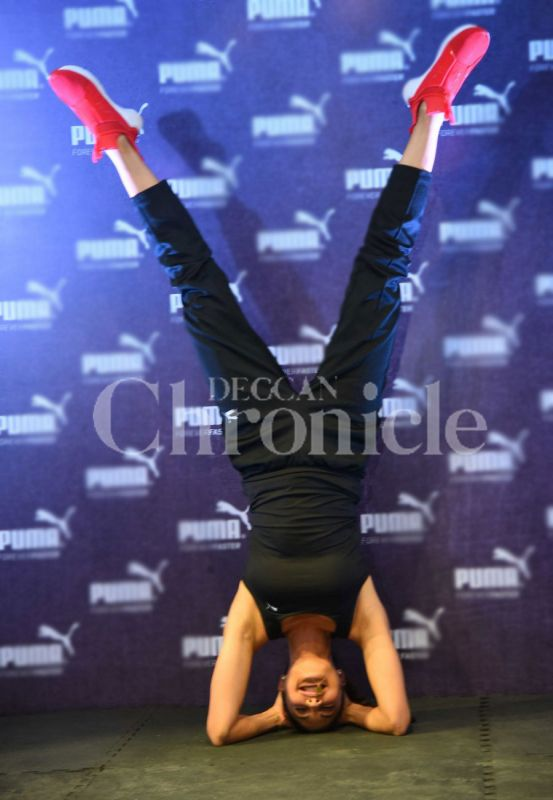 Jacqueline Fernandez performs a headstand at the event.
