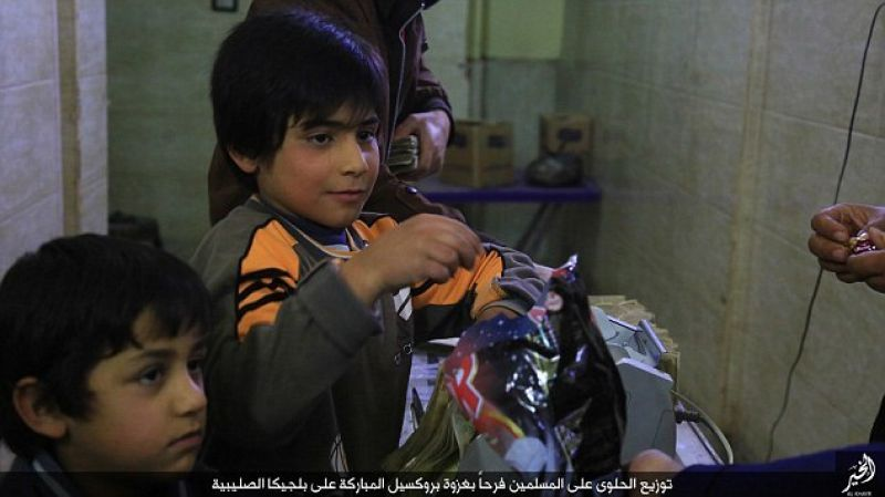 IS members distributed sweets to residents of Syria to celebrate the Brussels attacks. (Photo: SITE)