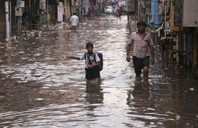 An schoolboy wades through a waterlogged street as it rains in Hyderabad. (Photo: PTI)