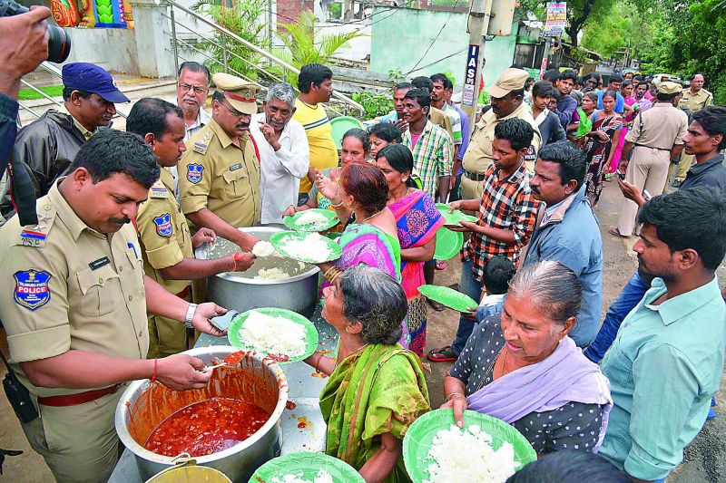Police personnel serve people food and milk after Nagamaiah Kunta was inundated in Wednesday's rains.